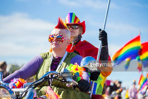 Couple riding bike during gay pride parade