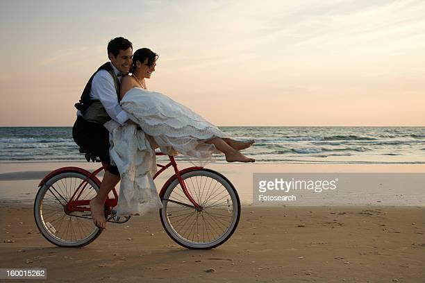 Couple Riding Bike on Beach