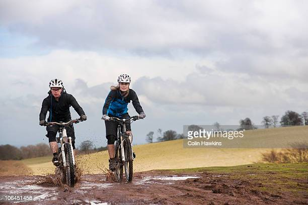 couple riding bike through muddy puddles - colin hawkins stock pictures, royalty-free photos & images