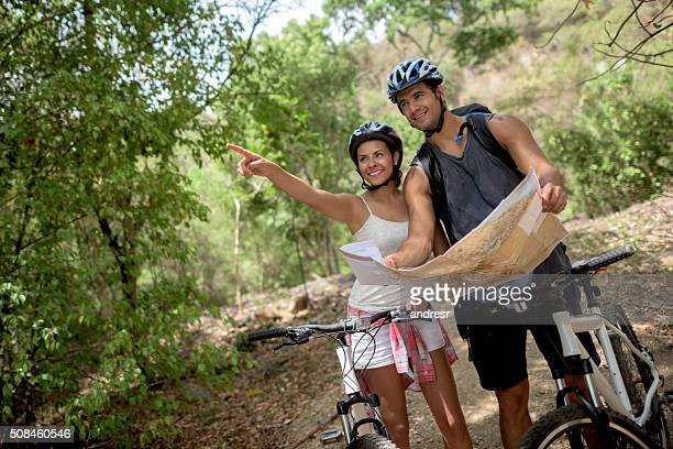 Couple riding bikes and holding a map