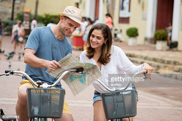 Couple riding bikes and looking at a map