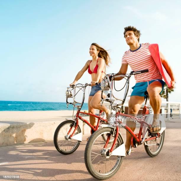 Couple riding bikes on beach boardwalk