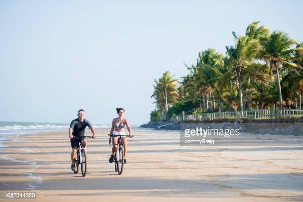 couple riding bikes on beach in brazil - trancoso imagens e fotografias de stock