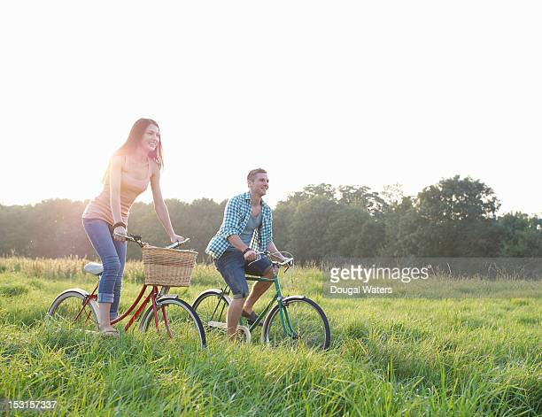 Couple riding bikes through Summer meadow.