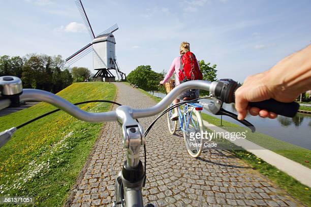 couple riding bikes towards windmill.