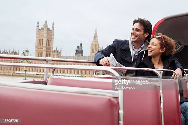 Couple riding double decker bus past Parliament Building in London