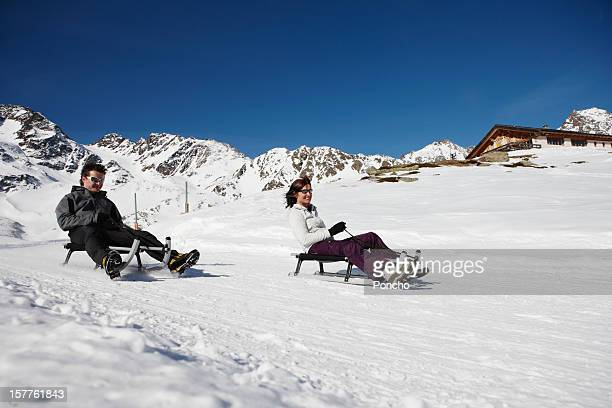 Couple riding down with a sledge