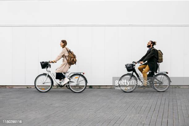 couple riding e-bikes along a white wall in the city - radfahren stock-fotos und bilder
