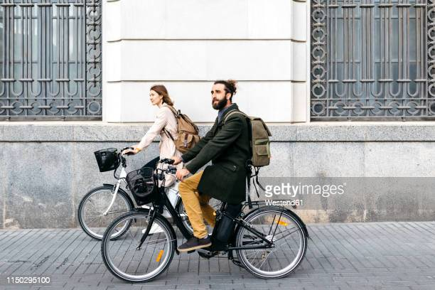 couple riding e-bikes in the city passing a building - moving past stock photos and pictures