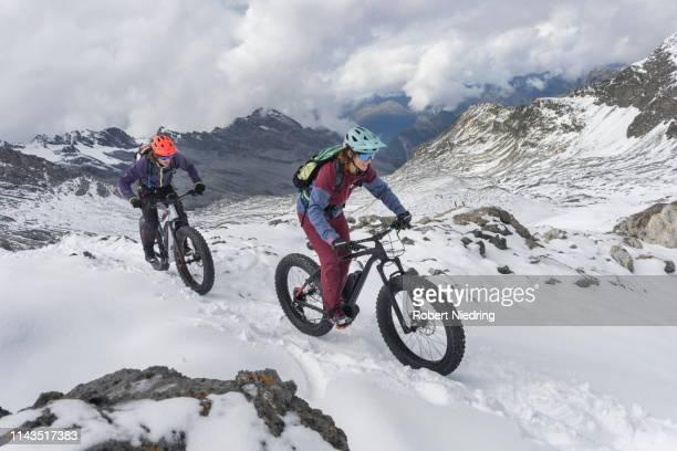 couple riding electric fatbikes on snowcapped mountain, passo di stelvio, lombardy, italy - partire bildbanksfoton och bilder