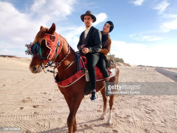 couple riding horse on sand - one animal stock pictures, royalty-free photos & images