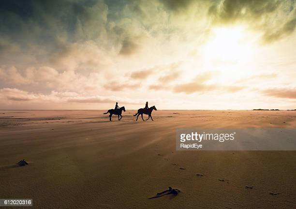 Couple riding horses across deserted sands at sunset