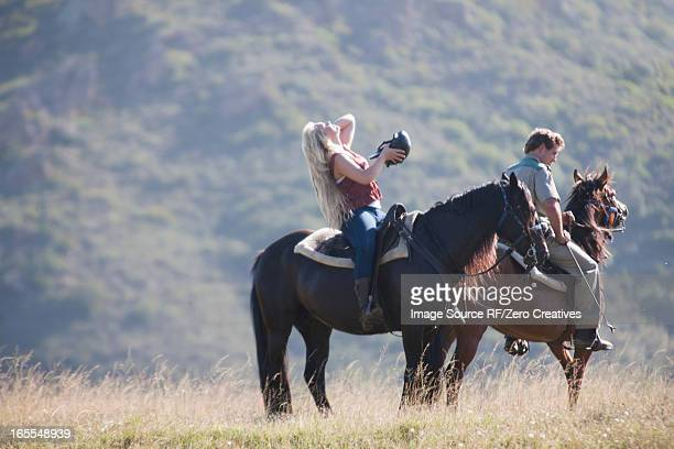 couple riding horses in rural landscape - mossel bay stock pictures, royalty-free photos & images