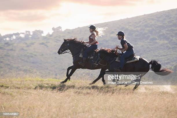 Couple riding horses in rural landscape
