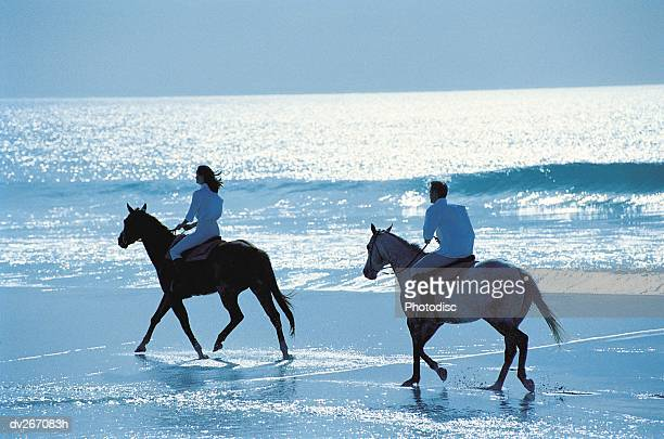 couple riding horses on beach - recreational horseback riding stock pictures, royalty-free photos & images