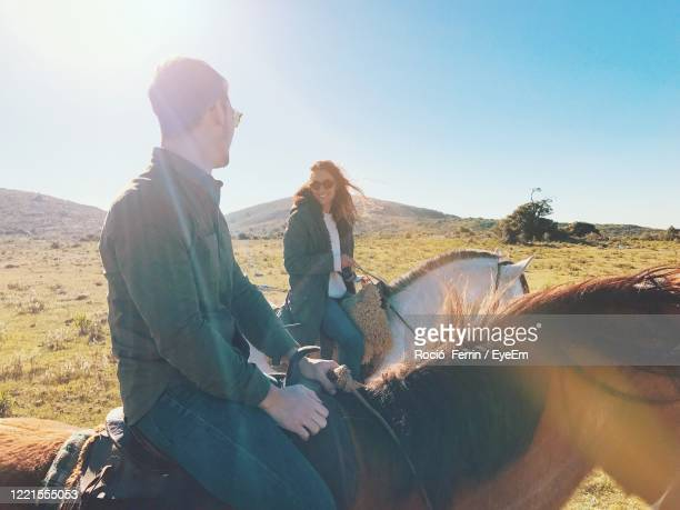 couple riding horses on land against clear sky during sunny day - uruguay stock pictures, royalty-free photos & images