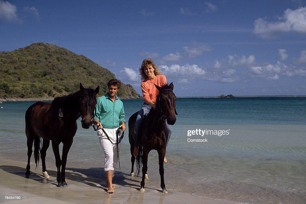 Couple riding horses on the beach : Stockfoto