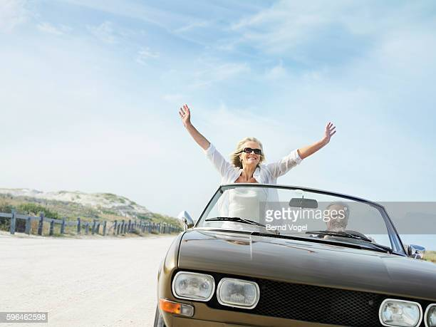 Couple Riding in Convertible Along Oceanfront Road