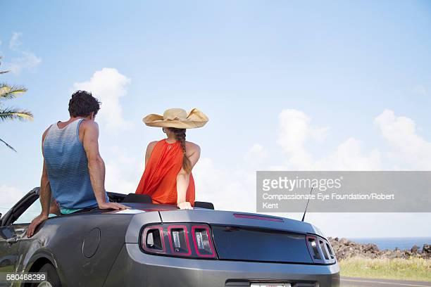 couple riding in convertible - パホア ストックフォトと画像