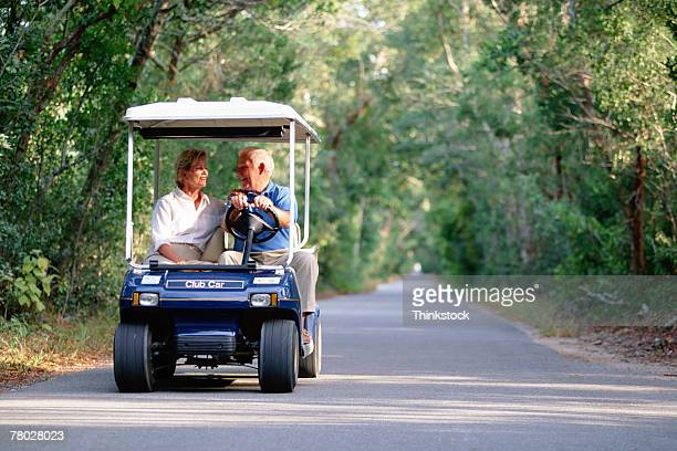 Couple riding in golf cart