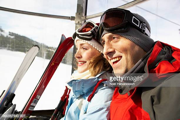 Couple riding in ski lift, smiling