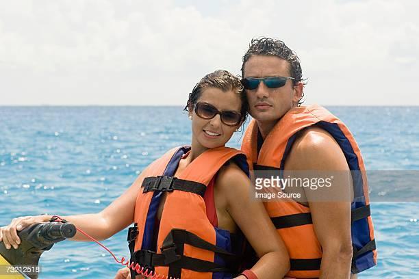 Couple riding jet ski