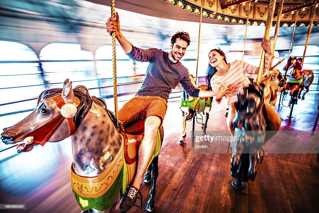 Couple riding merry-go-round in LA : Stock Photo