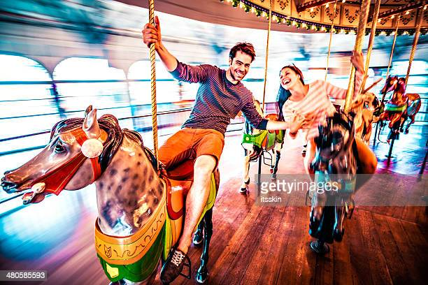 couple riding merry-go-round in la - amusement park ride stock pictures, royalty-free photos & images