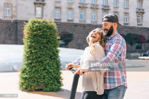 couple riding motor scooter in the city street - alternative fuel vehicle stock pictures, royalty-free photos & images
