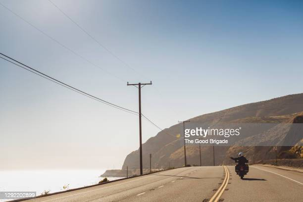 couple riding motorcycle on coastal highway during sunny day - california stock pictures, royalty-free photos & images