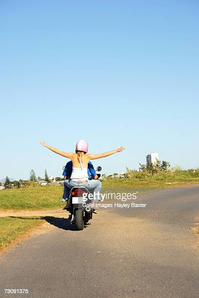 Couple riding motorcycle on country road, rear view