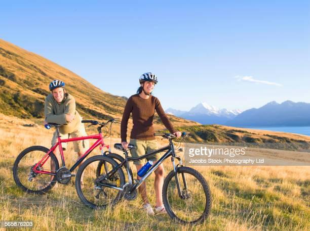 Couple riding mountain bikes in remote field