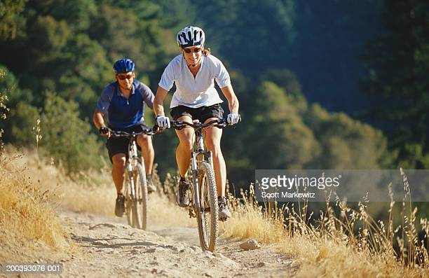 Couple riding mountain bikes on dirt trail