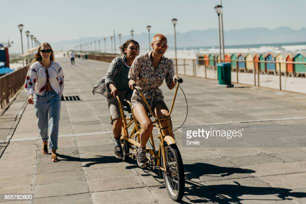 Couple riding on a tandem bicycle on the boardwalk