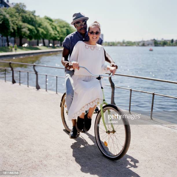 couple riding one bicycle together in city