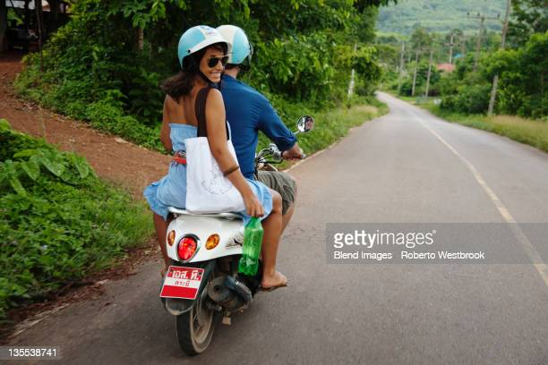 Couple riding scooter in remote area