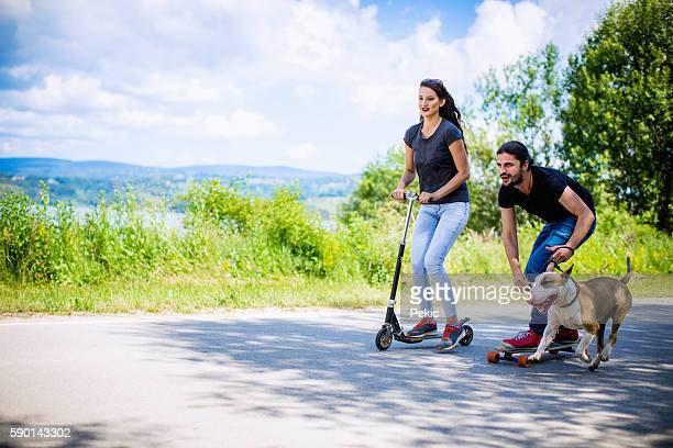 Couple riding scooter with their dog