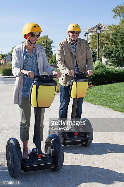 Couple riding segways in park, Philadelphia, Pennsylvania, USA