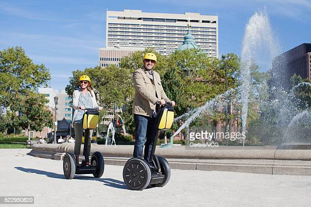 Couple riding segways past urban fountain, Philadelphia, Pennsylvania, USA