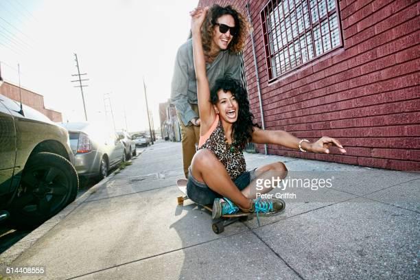 Couple riding skateboard on city street
