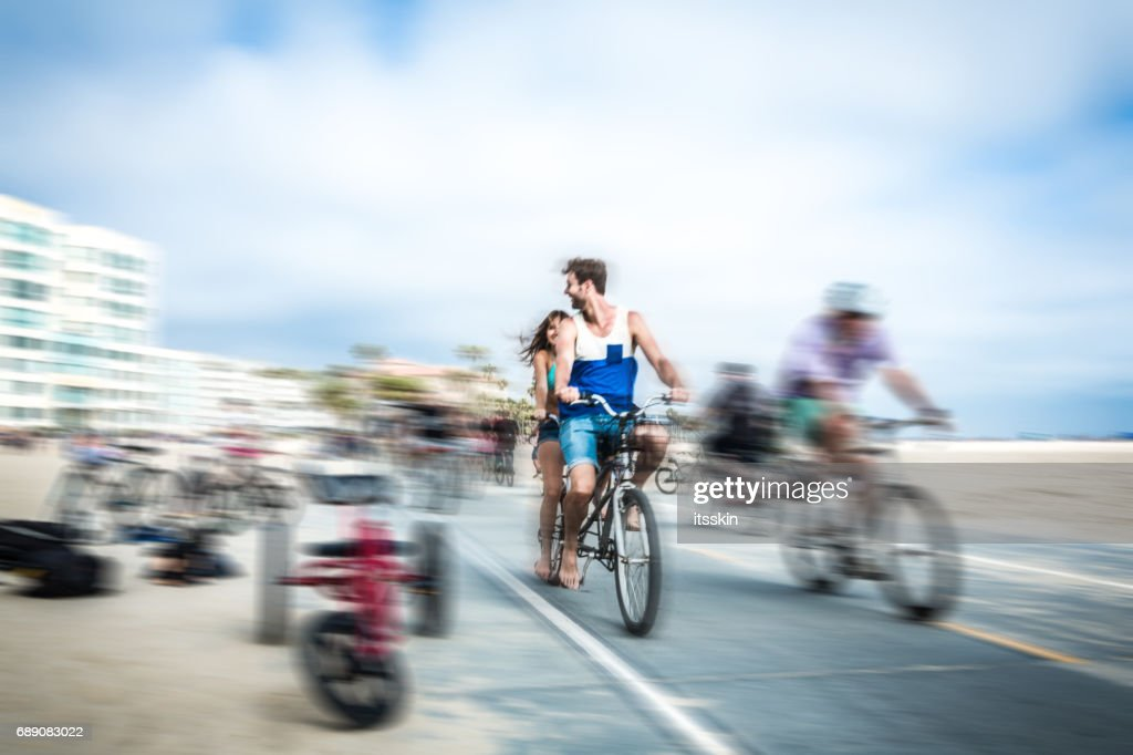 Couple riding tandem bicycle in LA. Blurred motion : Stock Photo