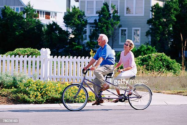 couple riding tandem bicycle - tandem bicycle stock pictures, royalty-free photos & images