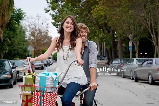 Couple riding tandem bike down street