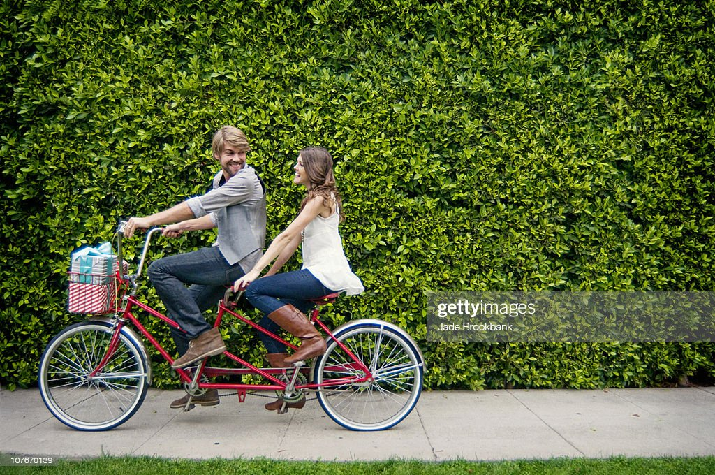 Couple Riding Tandem Bike In Front Of Hedge Stock Photo ...