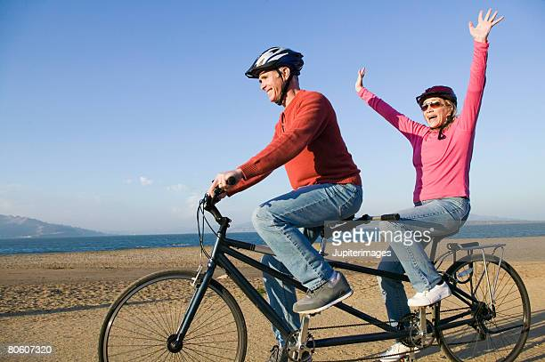 couple riding tandem bike - hands free cycling stock pictures, royalty-free photos & images