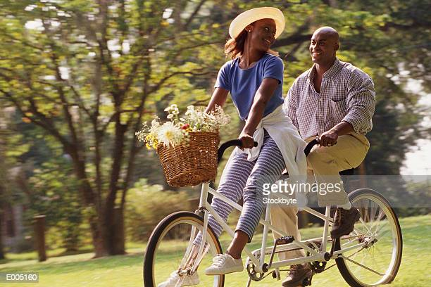 couple riding tandem bike together - tandem bicycle stock pictures, royalty-free photos & images