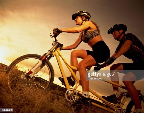 Couple riding tandem mountain bike