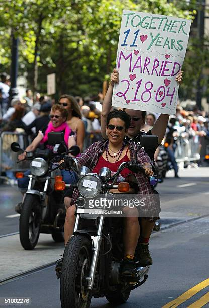 """Couple riding with the group """"dykes on bikes"""" carries a sign during the 2004 Pride Parade June 27, 2004 in San Francisco. Tens of thousands lined the..."""