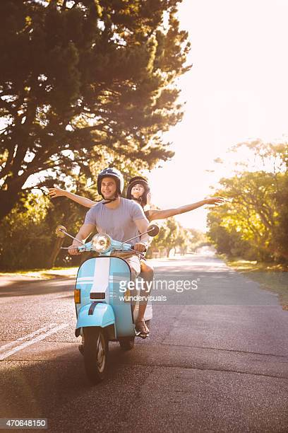 Couple road tripping on their scooter feeling free