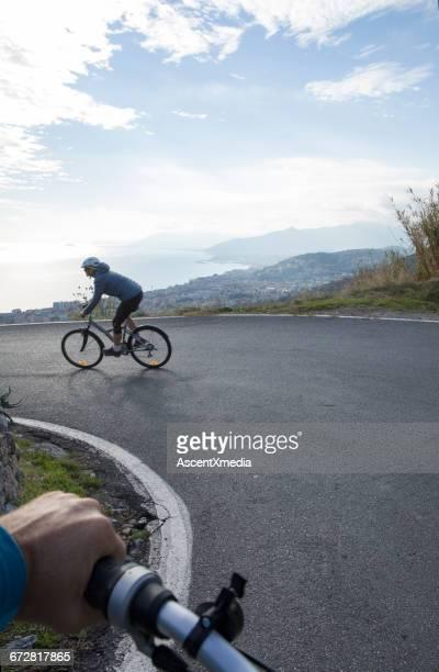 Couple roadbike towards village and sea